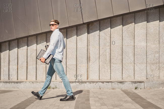 Full body side view of contemporary young male entrepreneur in casual outfit and sunglasses carrying paper folder and cup of takeaway coffee while walking against concrete wall of modern building