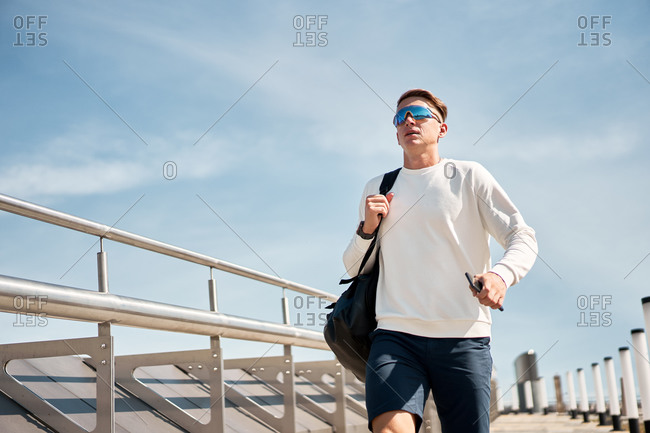 From below full body of confident young male in trendy casual outfit and sunglasses with bag over shoulder walking along urban street with contemporary buildings in background