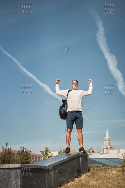 Low angle full body of young male in casual clothes with backpack raising arms and celebrating triumph while standing on border against blue sky with urban background
