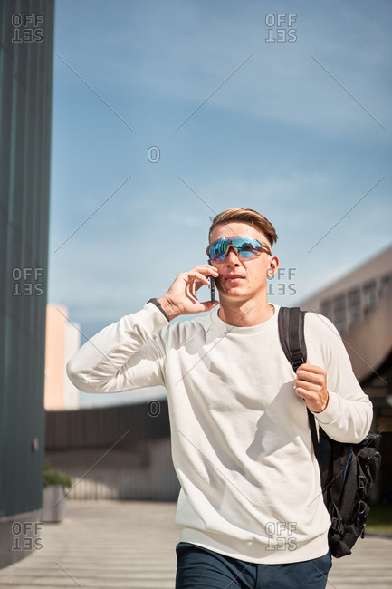 Confident young male in casual wear and trendy sunglasses with bag over shoulder walking on urban street and talking on mobile phone