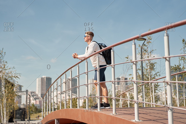 Side view of young male tourist in casual clothes and sunglasses with backpack leaning on railing of pedestrian bridge and looking away while resting after walking in city in summer day