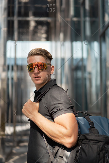 Side view of modern millennial active male with stylish haircut in trendy sunglasses and with backpack looking at camera while standing against blurred urban environment