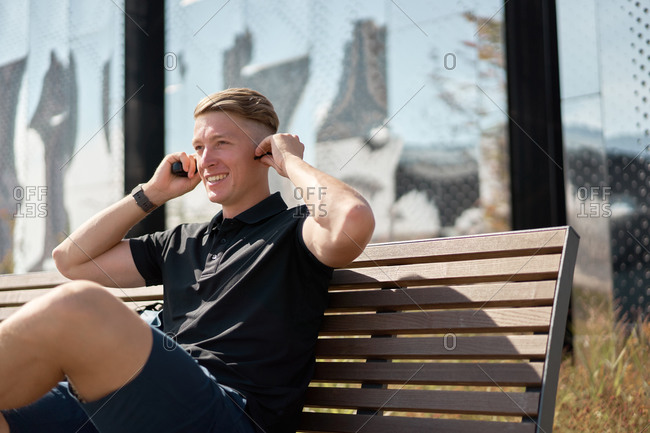 Low angle of confident young man in trendy casual outfit sitting on bench near backpack and putting on earbuds while resting on city street