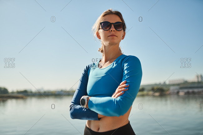 Low angle of confident young fit female in activewear and sunglasses with fitness tracker standing on river embankment and looking away