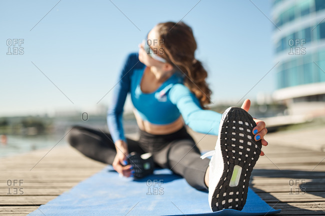 Unrecognizable slim female in activewear and sport shoes sitting on mat and stretching legs during outdoor fitness workout on urban embankment