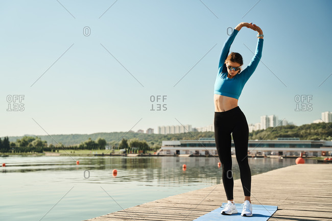 Full body of young fit female in sportswear and sunglasses stretching arms while warming up during fitness workout on wooden pier near river