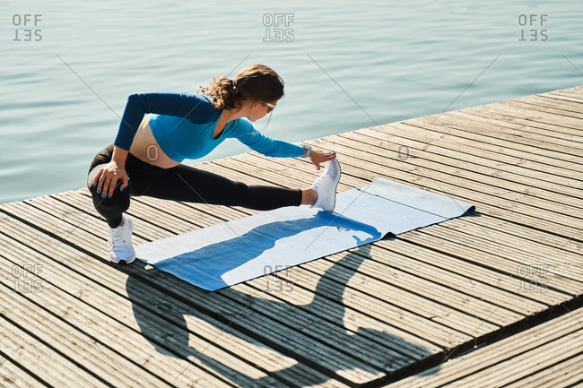 From above active slim female in sportive outfit standing on mat and doing stretching exercise for legs while training on wooden pier near river
