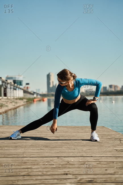 Active slim female in sportive outfit standing on mat and doing stretching exercise for legs while training on wooden pier near river