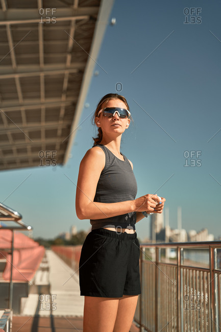 Side view of young fit female in activewear and sunglasses putting on earbuds while standing at stadium and preparing for outdoor workout