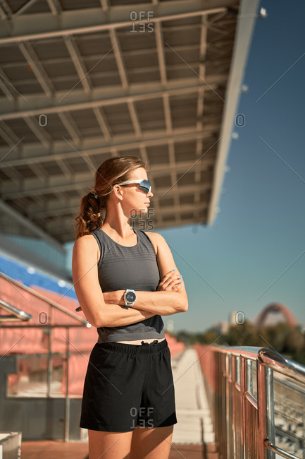 Low angle of confident young fit female in black sportive outfit and trendy sunglasses standing near metal railing at stadium and looking away