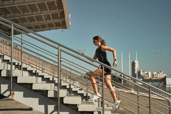 Low angle side view of energetic determined female athlete in sportswear running upstairs on tribune of stadium during outdoor fitness training