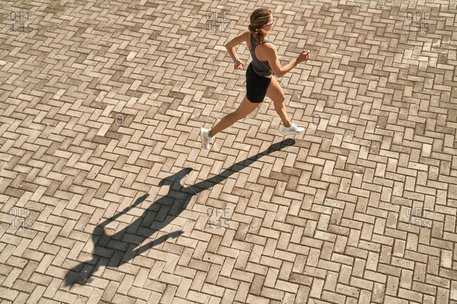 From above full body of active slim female in sportswear running fast on paved square in sunny day