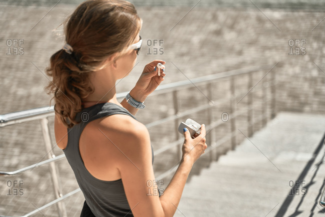 From above back view of unrecognizable fit female in activewear and sunglasses putting on earbuds while standing on stairs and preparing for outdoor workout