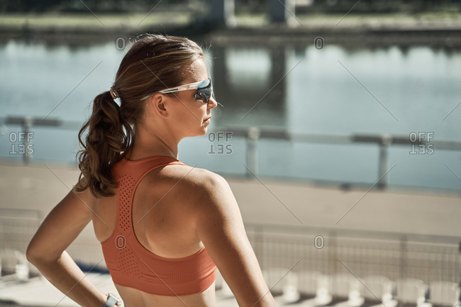 Back view of unrecognizable slim female athlete in sportswear standing on urban embankment near river and relaxing after exercising in summer day