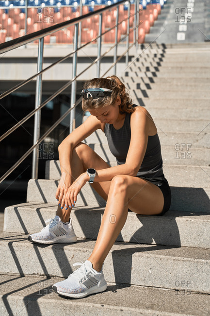 Full length of tired young athletic female in sportswear and sneakers sitting on stone steps near tribune and taking rest after running workout at stadium