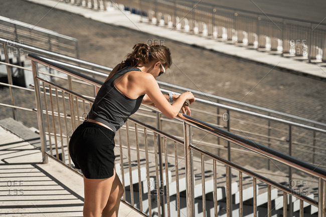 Side view of tired young sportswoman in black sportive outfit and sunglasses leaning forward on railing on stadium tribune while resting after outdoor workout