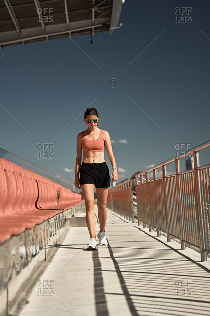 Full body of determined young sportswoman in activewear and sunglasses walking along tribune of stadium against blue sky
