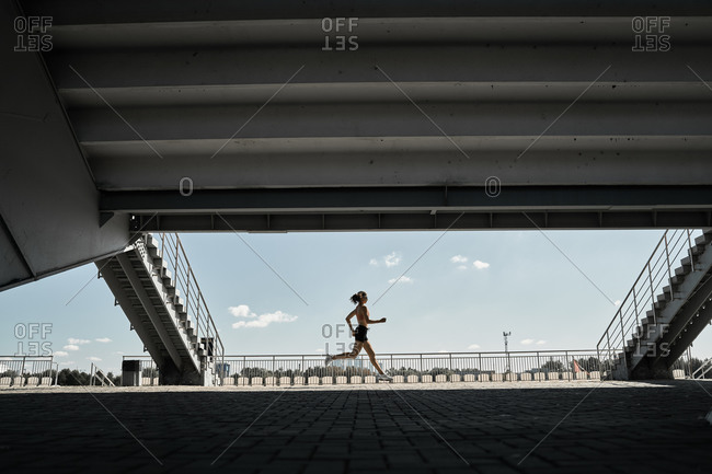 Side view of determined female athlete running fast during outdoor workout near stairways of stadium