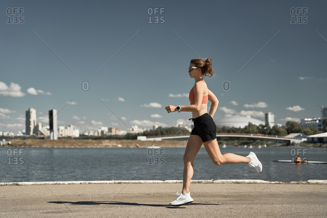 Side view full body of energetic motivated fit female in activewear with fitness tracker jogging on paved embankment near river in city