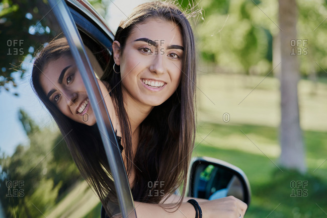 Cheerful female sitting on passenger seat and looking at camera out of window of modern automobile parked in garden in summer