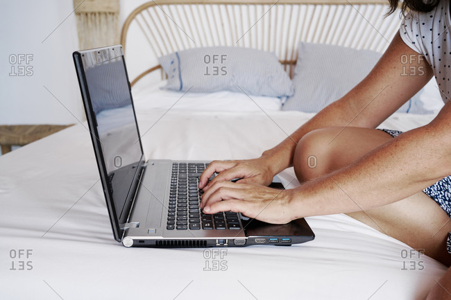 Cropped unrecognizable female freelancer sitting on bed in room and working on remote project while using netbook