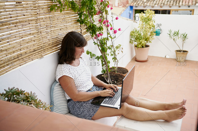 Side view of focused female entrepreneur in casual wear sitting in apartment terrace and working on remote project online while using netbook