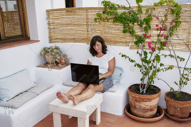 Focused female entrepreneur in casual wear sitting in apartment terrace and working on remote project online while using netbook