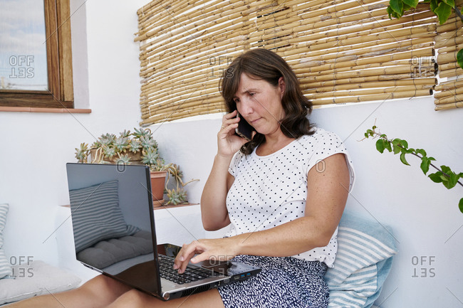 Busy adult female entrepreneur sitting on terrace in summer and working remotely while discussing project on cellphone and typing on netbook