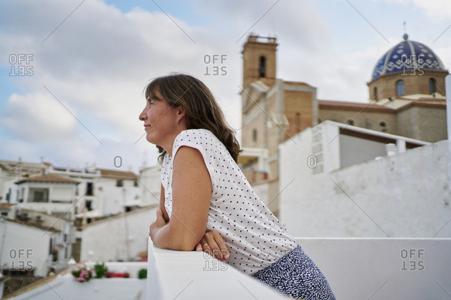 Side view of female standing on balcony and admiring amazing seascape in Altea during summer vacation looking away