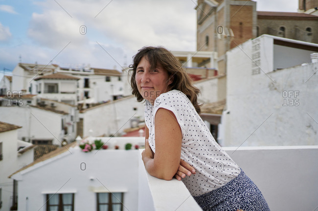 Side view of female standing on balcony and admiring amazing seascape in Altea during summer vacation looking at camera