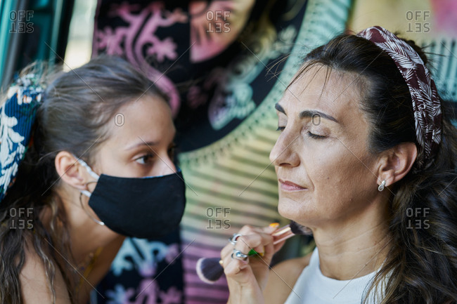 Female artist with face mask applying foundation with brush on face of mature female while doing stylish makeup