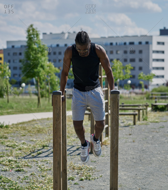 Determined African American male athlete with naked torso balancing on parallel bars and doing abs exercises during intense workout on sports ground in summer