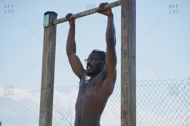 Tense determined young African American sportsman with naked torso doing bar muscle up exercise during calisthenics workout on sports ground