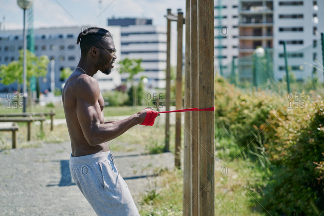 Side view of athletic muscular African American sportsman performing pull exercise with resistance band while training upper body muscles during calisthenics bodyweight workout on street