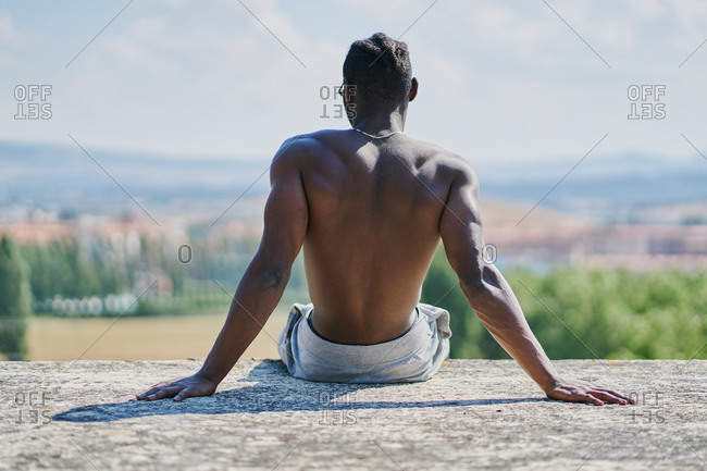 Back view of unrecognizable shirtless African American sportsman sitting on ground against blurred city and mountains while relaxing after fitness training