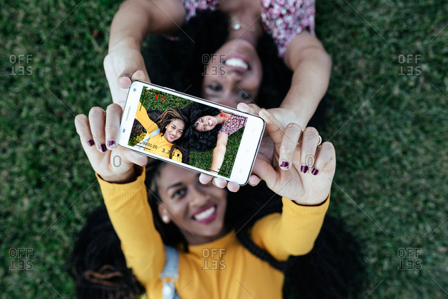 Top view of cheerful female best friends lying on green grass together and taking photo on smartphone camera while enjoying weekend
