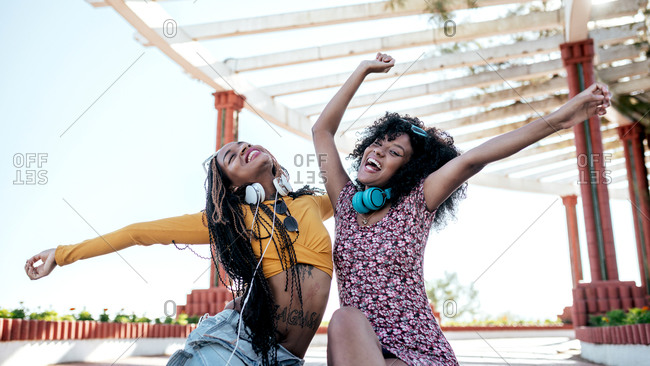 Cheerful black female friends with braids and curly hair sitting on embankment and having fun with raised arms in summer