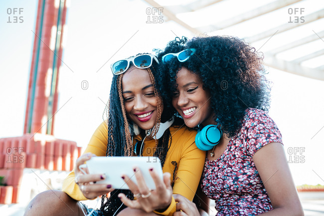 Laughing African American female with curly hair and black woman with braids sitting on promenade in summer and watching funny video together on cellphone