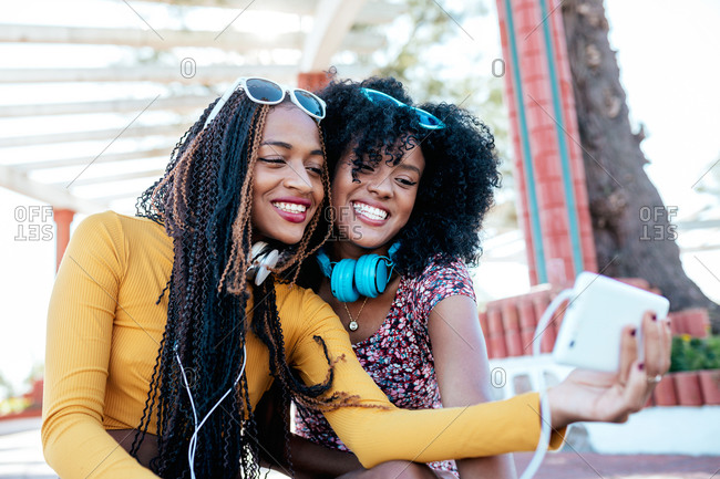 Smiling black woman with braids hugging cheerful African American female friend with curly hair and taking selfie together while standing on promenade in summer