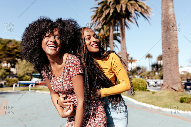 Side view of black woman with curly hair hugging delighted African American female friend with braids while standing on embankment and looking away