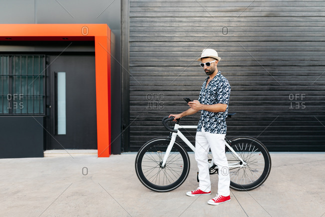 Side view of serious male in trendy wear standing with bike on street and browsing mobile phone in city