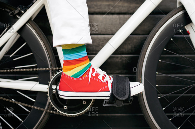 Unrecognizable crop person wearing colorful striped socks sitting on modern bicycle in city
