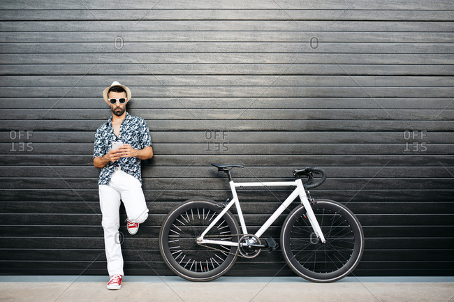 Serious male in trendy wear standing near bike on black wall and browsing mobile phone in city