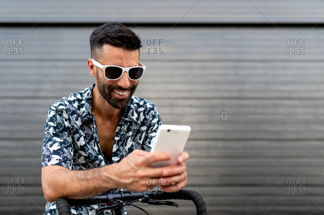 Delighted male in stylish outfit leaning on handlebar of bicycle and reading messages on social media via mobile phone in city