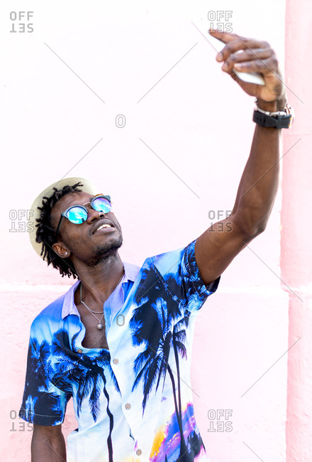 Delighted ethnic male wearing stylish shirt with tropical print standing near building in city and taking selfie on smartphone