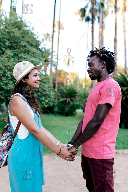 Side view of loving multiracial couple of travelers standing in park with palms and holding hands while looking at each other