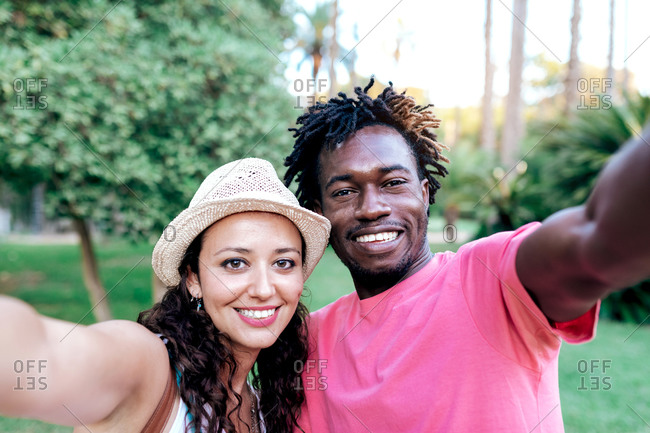Cheerful multiracial traveling couple hugging and taking selfie on smartphone while standing in green tropical park during summer vacation