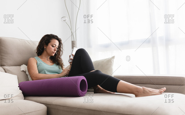 Side view of calm female lying on soft couch in modern living room and browsing cellphone during weekend at home