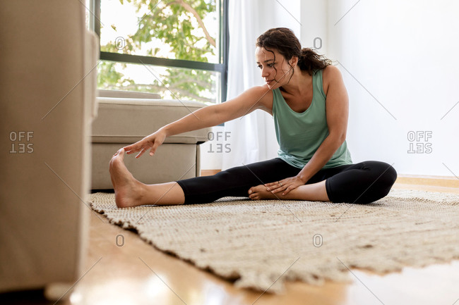 Peaceful female in sportswear practicing yoga in Seated Forward Bend pose and stretching legs while sitting on carpet in living room