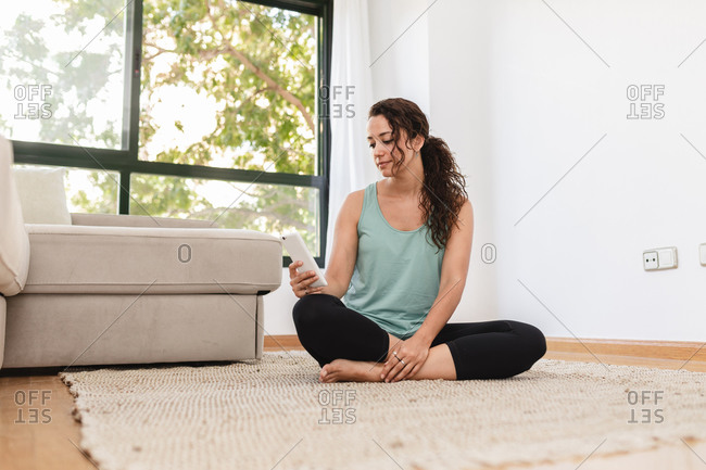 Calm female in domestic outfit sitting with crossed legs on floor and messaging on social media via mobile phone at weekend